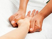 massage therapist gently pressing female hand