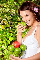 Girl eats an apple with bowl of apples in a summer garden