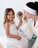 Mother applying blusher with her daughter in bathroom
