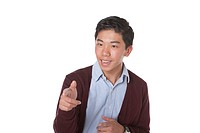 Studio portrait of young Asian American student on white background pointing