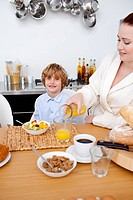 Kid having breakfast with his mother in kitchen