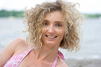 Portrait Of A Mature Blonde Woman With Curly Hair Near Water Side