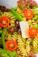fresh healthy homemade italian fusilli pasta salad with parmesan cheese,pachino cherry tomatoes, black olives and mix vegetables ,dressed with extra_v...