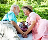 Senior couple on romantic picnic, flirting with each other.