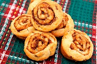 Little cinnamon pastries on red, green and white fabric