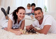 Happy couple playing chess on floor in living_room with their children on sofa