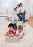 Children using a laptop on floor in living_room with their parents on sofa