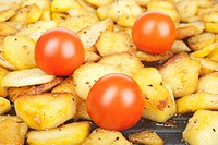 Fried potatoes and tomatoes in a pan