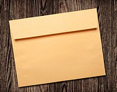 Golden envelope on wooden background, clipping path, studio shot