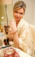 Woman sitting at the dressing table and putting on a bracelet (thumbnail)