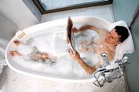 Man relaxing in bathtub with bubbles