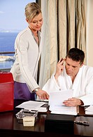 Two business people working in a hotel room