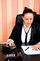 Saleswoman using calculator and looking on paperwork in office