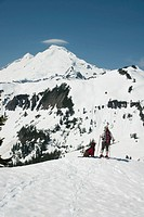 A female snowshoer and her dog pause for a scenic view of Mt. Baker in northern Washington