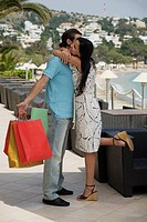 Woman embracing man holding shopping bags