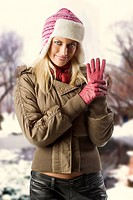 beautiful blond girl wearing a winter breakwind jacket scarf gloves and pink hat