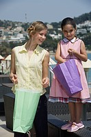 Mother and daughter looking in shopping bags (thumbnail)