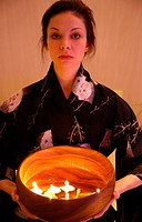 Young woman holding wooden bowl with burning candles