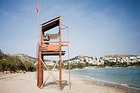 Businessman on life guard stand with binoculars