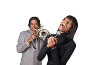 Studio portrait of two young attractive African American performers on white background singing with joy and playing the trombone