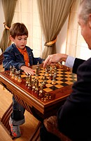 Mature man and little boy playing chess (thumbnail)
