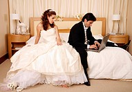 Bride waiting for groom to get off his laptop