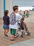 Midget parents push their normal size daughter in a stroller at Laguna Beach, CA.