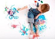 Cute 5 years old boy painting on white background