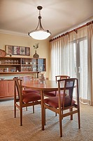 Dining room table and chairs in a dining room. Modern wooden furniture. Lamp and bookshelves. Thousand Oaks, California, USA. Traditional decorative s...