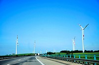An image of Highway and wind turbines in the foreground