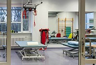 Rehabilitation Center, Treatment and equipment in a large room. Table, treatment couches, electronic adjustable beds, and moving hoists with red sling...