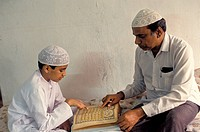 India. Muslim Boy Reading Holy Book With The Help Of His Father