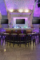 Round bar stand against three TV screens on brick wall lighted in purple