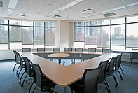 Large empty boardroom. A long narrow table in a triangle formation with a gap at the centre. A view from the windows out on to Vancouver city.