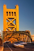 Tower Bridge, Sacramento, California, USA. A road bridge with tall towers and a metal framework arch. Cars on the road. Transport