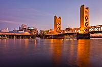 Tower Bridge over the Sacramento River, Sacramento, California, USA. Sunset over the city. Bridge with two tall towers. Downtown buildings. Reflection...