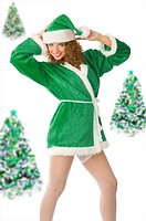 cute model in green santa claus dress with christmas tree in background