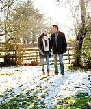 young couple walking through garden in winter