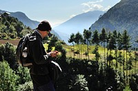 hiker in Nepal checking his GPS device