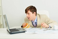 Funny man with big sandwich at office