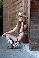 Seated young woman posing in jeans hot paints, hat and cowboy boots, western style