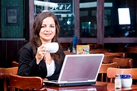 young smart business woman working on laptop computer in a cafe