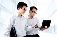 Two Asian young executives working on laptop, office building as background