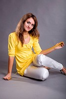 beauty girl in yellow blouse on gray