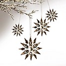 Silver snowflakes hanging against pale grey background
