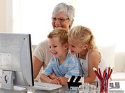 Children using a computer with their grandmother at home