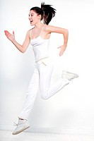 beautiful young woman on studio isolated white background doing her workout run leap