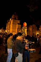 Mexico, Oaxaca, Oaxaca City. Merriment on the Zocalo on Christmas Eve with large ´monos´ in procession, fireworks, brass and, and women dancers dresse...