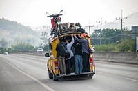 Overcrowded share taxi or Songthaew on a road, a motor bike loaded on the roof, northern Thailand, Thailand, Asia