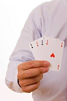 A busiines man holding four playing cards with aces